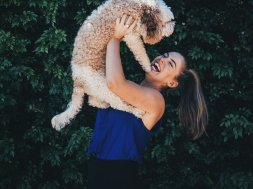 Une fille qui rit aux éclats tenant un chien à bout de bras.